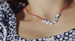 Camera tilts towards beads on a female neck spelling out the word Love - stock footage
