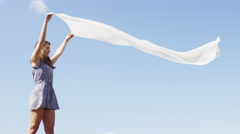 Young woman holding her scarf as it flutters in the breeze, in slow motion Stock Footage