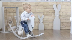 Baby sitting on the toy horse Stock Footage