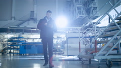 Mechanic Moving Through Aircraft Maintenance Terminal and Greeting Colleague - stock footage