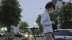 Young Guy With Long Hair Riding Using Smart Phone Navigator In City With Bike Stock Footage