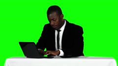 Businessman sitting at a desk and using laptop. Office work. Green screen - stock footage