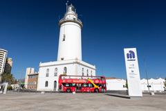 MALAGA, SPAIN - SEPTEMBER 4 2014: White lighthouse and turistic bus Stock Photos
