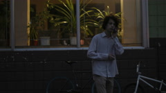 Young Guy With Long Hair Talking Via Phone At Night City Bike BMX On Background Stock Footage