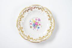 antique plate with floral pattern and decorative rim - stock photo