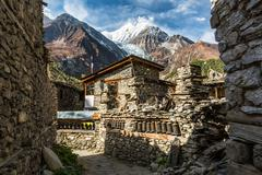 Traditional stone build village of Manang. Mountains in the background. Stock Photos