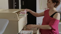 Pregnant woman puts baby clothes Stock Footage