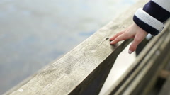 Girl leaning on wooden railing at the lake Stock Footage