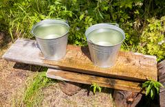 Metal buckets with cold water standing on a bench at the village water well - stock photo