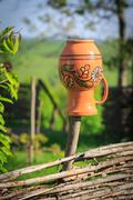 clay jug on wooden fence - stock photo