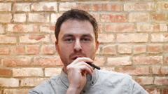 A young man smokes an e cigarette indoors - stock footage