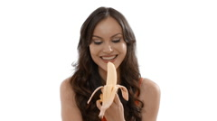 Young woman eating a banana indoors against a white background Stock Footage