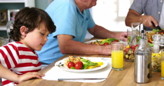 Happy multi-generation family eating at table Stock Footage
