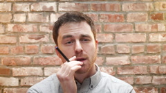 A young man smokes an e cigarette indoors Stock Footage