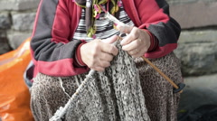 Street seller old woman knitting sweater on street, close up Stock Footage