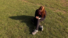 Female sitting in grass using smart phone outdoors 4k Stock Footage