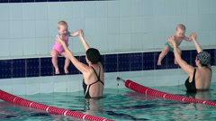 Mothers teach their children swimming in the pool. - stock footage