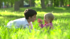 The boy and the little girl play on a grass in park - stock footage