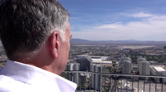 Confident businessman looking over edge of balcony upon city 4k Stock Footage