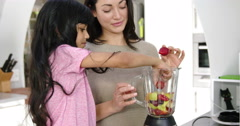 Happy mother and daughter making smoothies Stock Footage