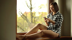 Cute girl sitting on windowsill and writing message on cellphone Stock Footage