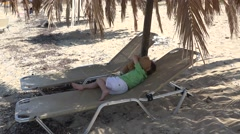 Little child holding a teddy bear trying to sleep at palm tree shadow on beach Stock Footage