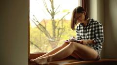 Young woman write, sitting on windowsill - stock footage