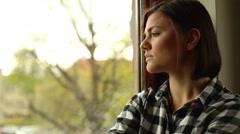 Sad woman sitting near window - stock footage
