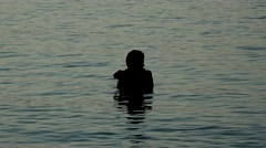 Young lovers hold their bodies tight in the sea at sunset Stock Footage
