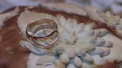 Two splendid wedding rings on Almond banana bread isolated on white background Stock Footage