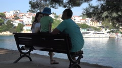Young family sitting on bench near Greek port, white village Stock Footage