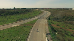 A guy goes on a skateboard on a deserted road. Aerial shot.N. - stock footage