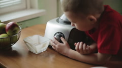 A small boy switching on a blender and watching it Stock Footage