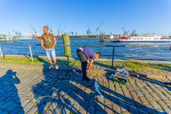HAMBURG, GERMANY - JUNE 08, 2015: Stone port on Hamburg, fisherman with one fish - stock photo