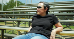 Woman relaxing on bleachers medium - stock footage