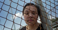 Depressed woman behind a fence - stock footage
