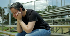 Depressed woman sitting on bleachers dolly left - stock footage