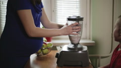 A woman adjusting a jar and switching on a blender Stock Footage