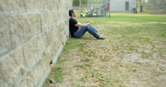 Sad woman sitting against a wall long shot Stock Footage