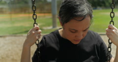 Sad woman on a swing dolly right - stock footage