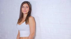 Young Attractive Female Smiling Doing Different Poses Against White Wall Stock Footage