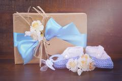 Baby Shower Gift with Booties on Dark Wood Stock Photos
