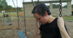 Sad woman on a swing hangs her head - stock footage