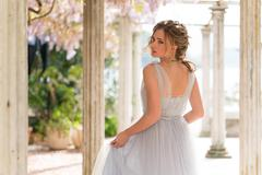 Young bride in a wedding dress poses on the terrace Stock Photos