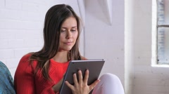 Female In Orange Sweater Using Tablet Sitting In Front Of A White Brick Wall Stock Footage