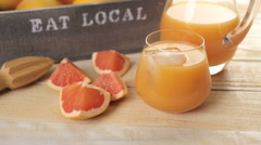 Organic ruby red grapefruit juice in small glass with ice. - stock footage