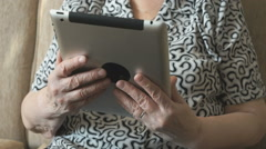 An old woman viewing photos using a digital tablet Stock Footage