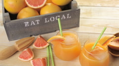 Organic ruby red grapefruit juice in small glass with ice. Stock Footage