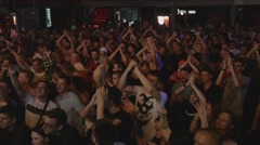 Teenagers on discotheque in nightclub. Applaud. Spotlights. Raise hands. Live - stock footage