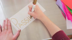 Female Hands Writing Passion On A White Piece Of Paper Stock Footage